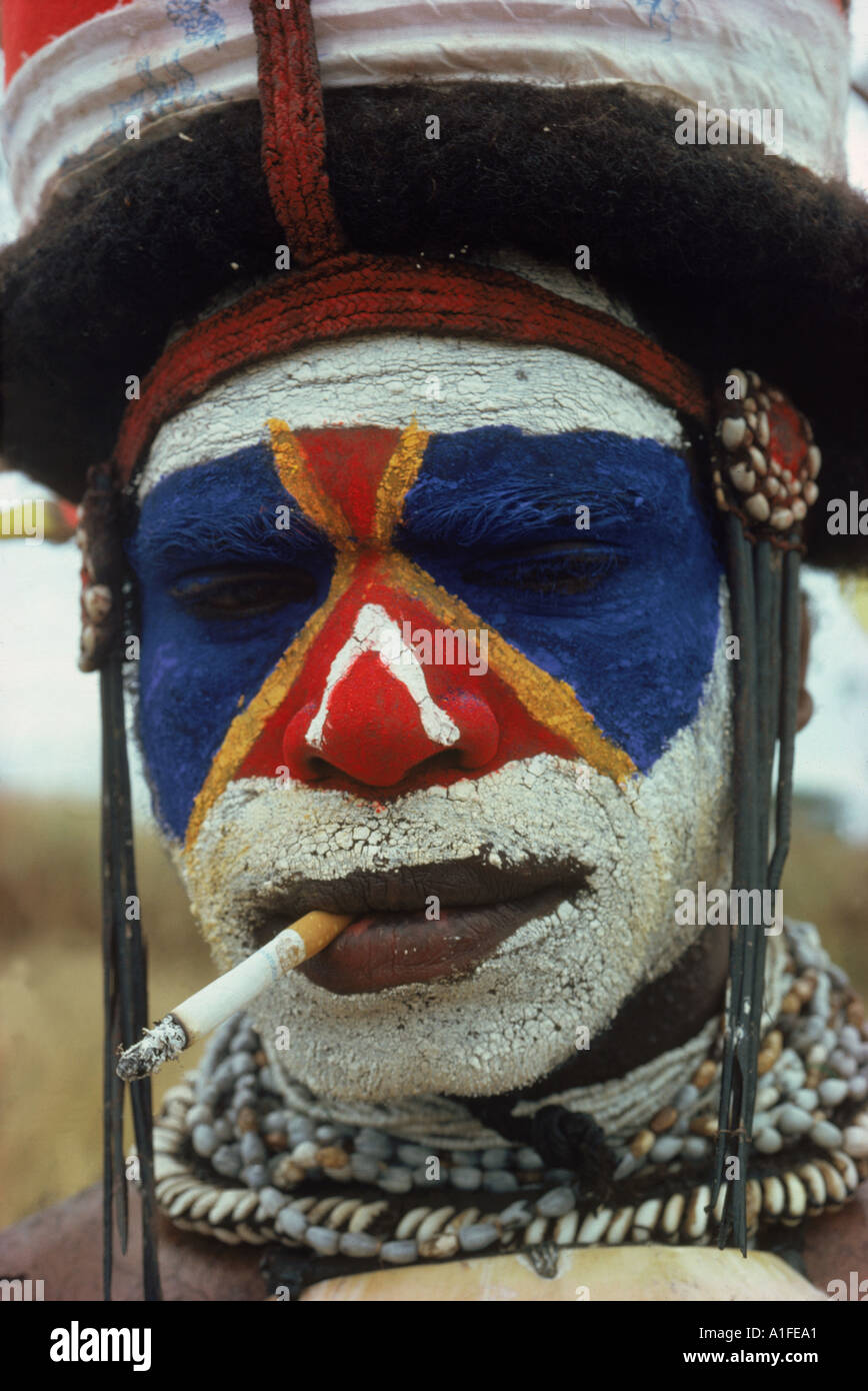 Portrait of a South Highlander at Mendi with bright facial decoration and smoking a cigarette Papua New Guinea Pacific Islands - Stock Image