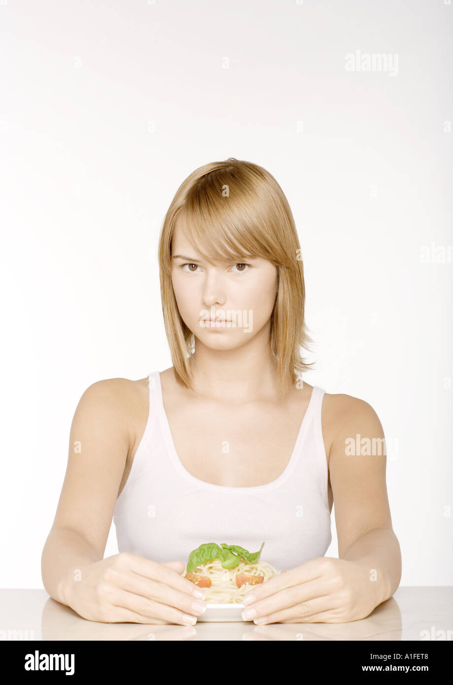 Young woman with arms around plate of pasta - Stock Image