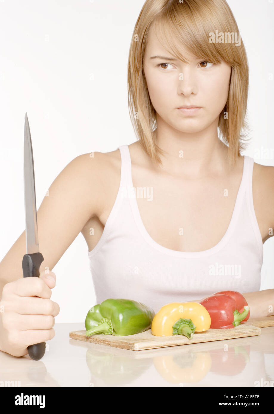 Young woman holding up knife in front of bell peppers - Stock Image