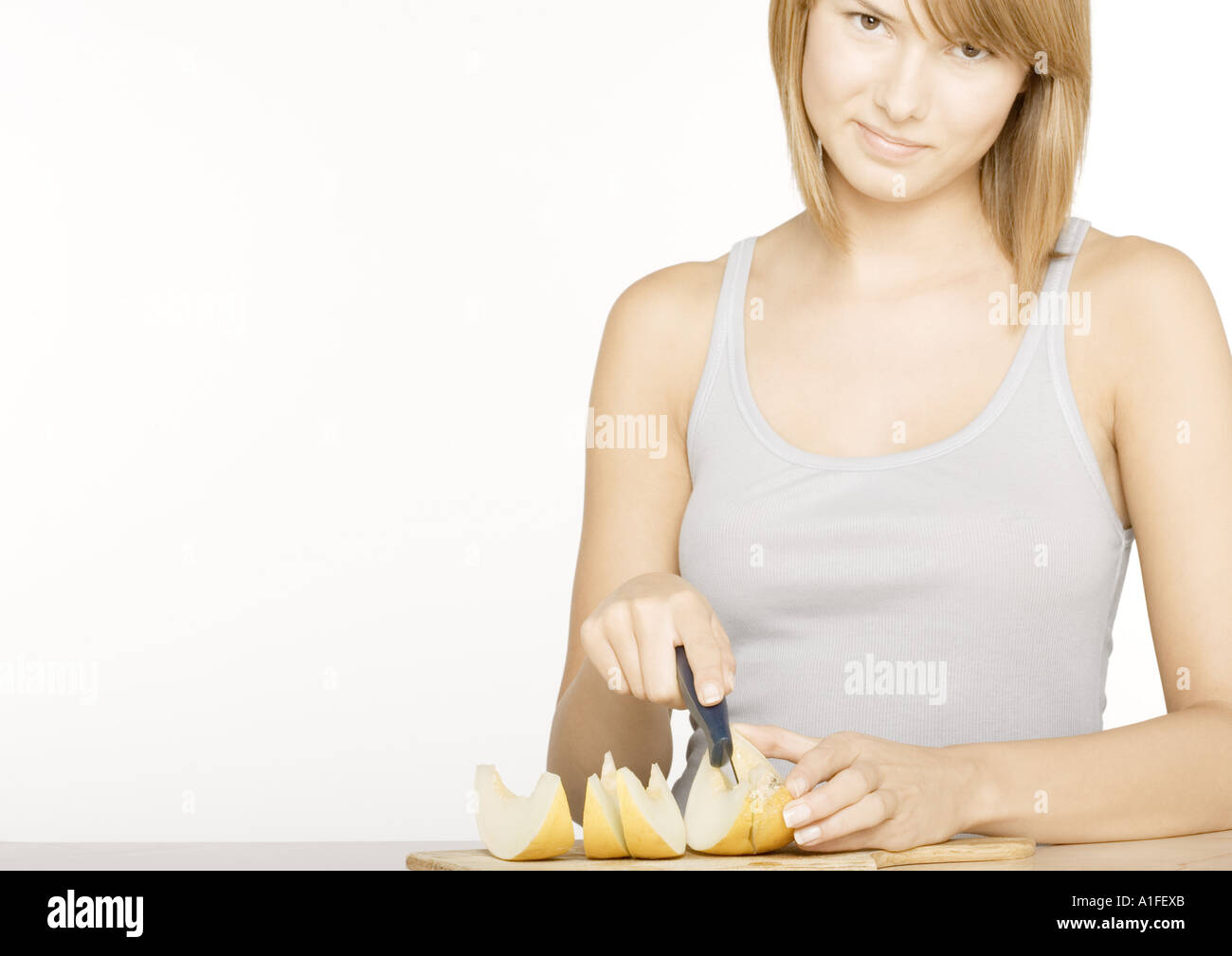 Young woman cutting up melon - Stock Image