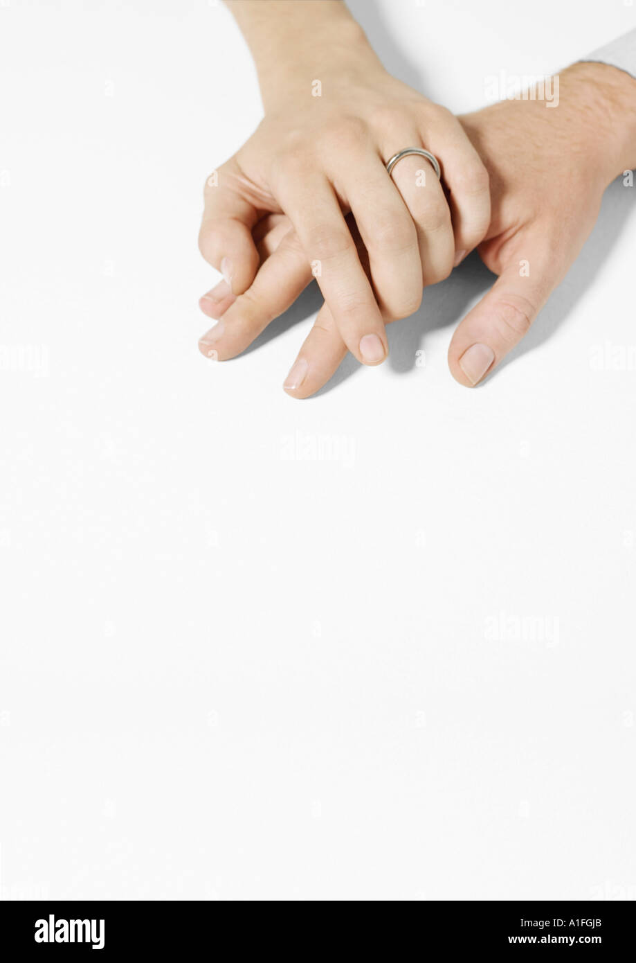 Woman wearing wedding ring clasping man's hand - Stock Image