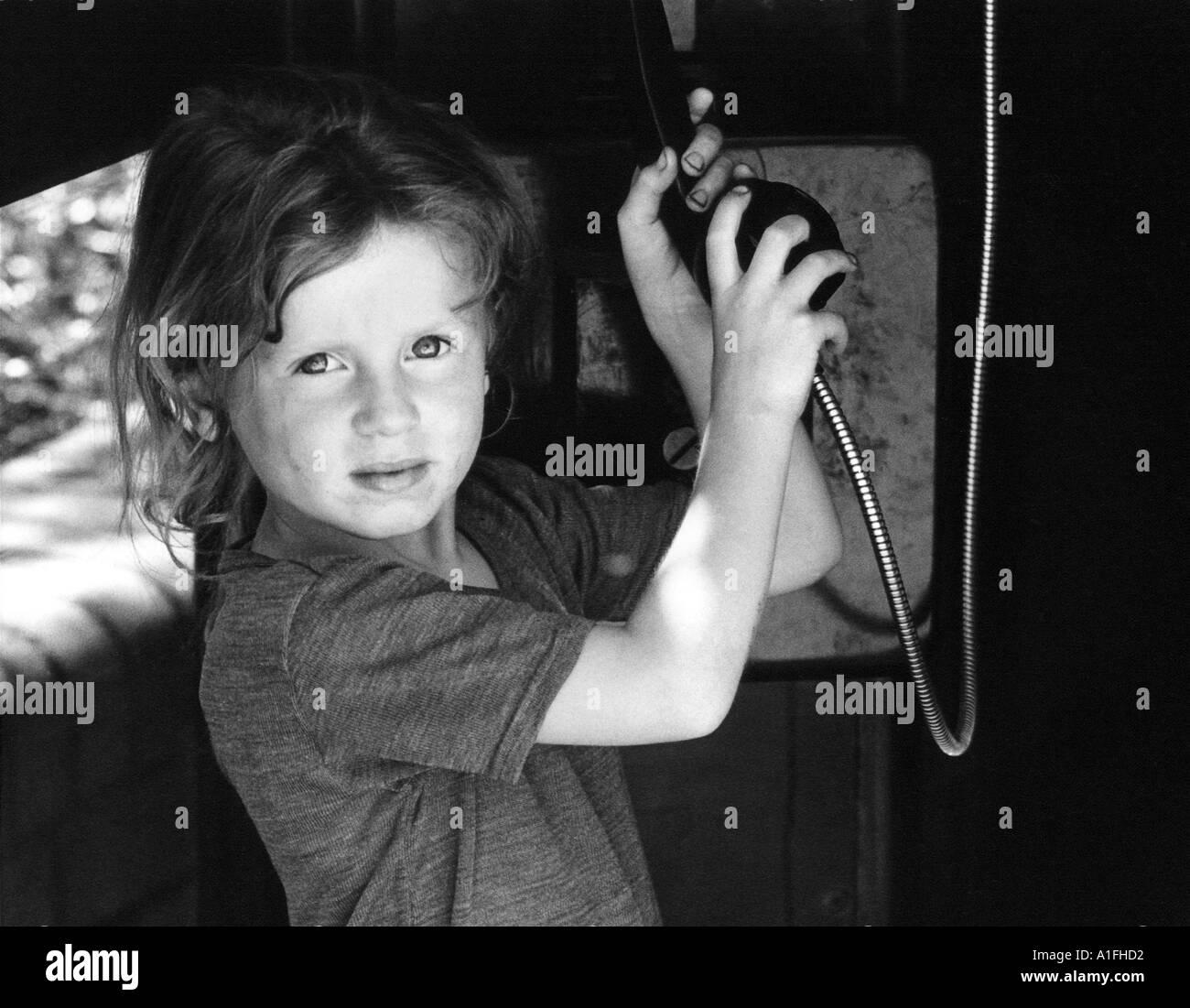 Child reaching for telephone in street kiosk - Stock Image