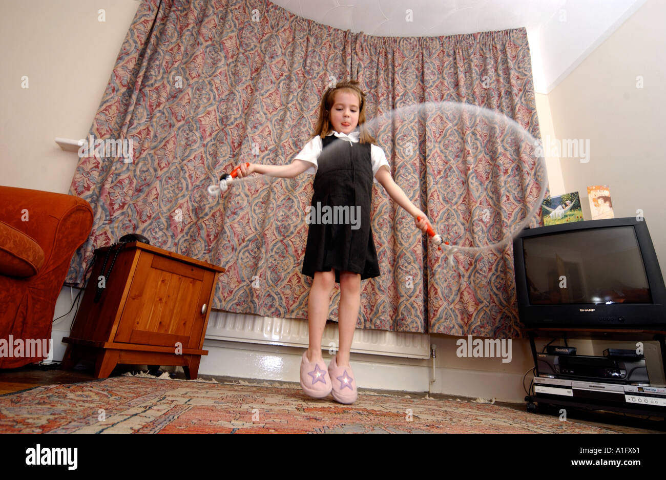A girl playing with a skipping rope indoors - Stock Image