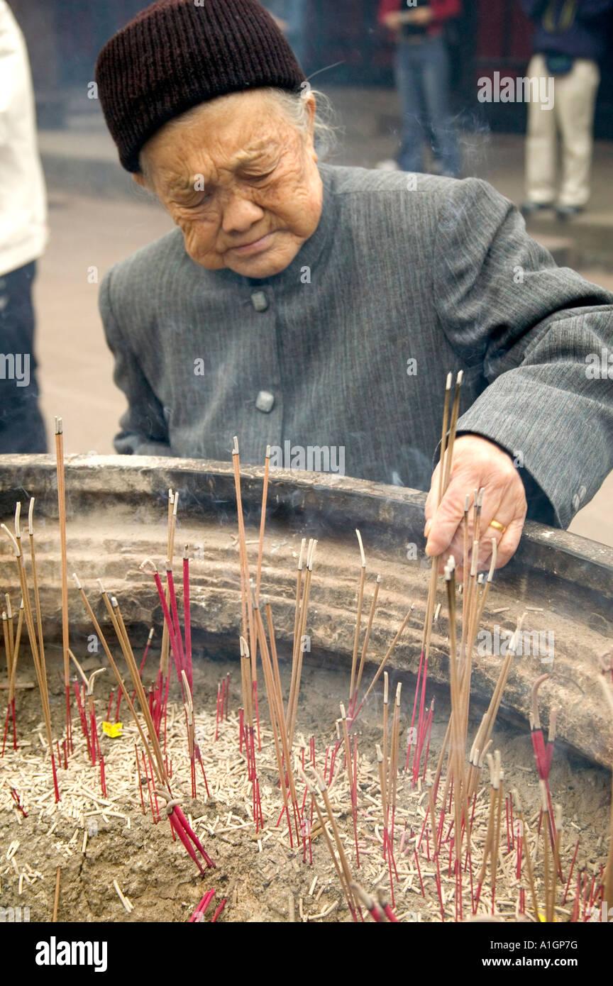 Senior woman burning incense at temple, China - Stock Image