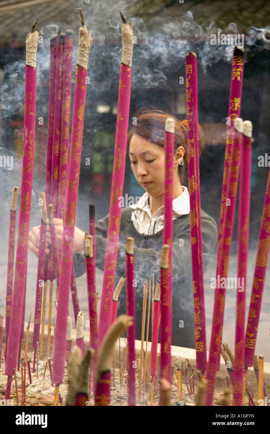 Young woman lighting incense at temple, Sichuan Province, China - Stock Image