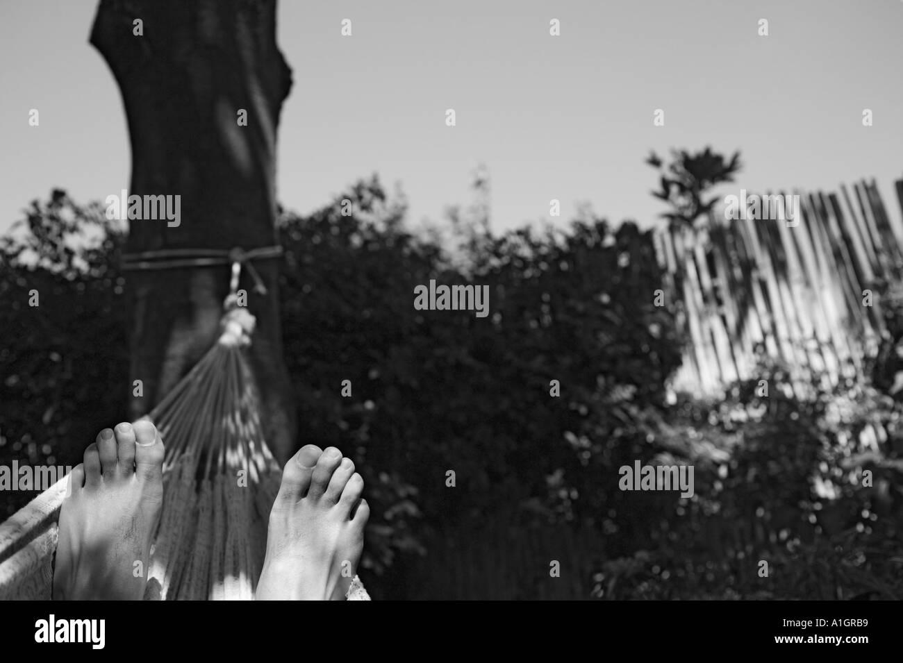 Feet Of Man Resting In Hammock - Stock Image