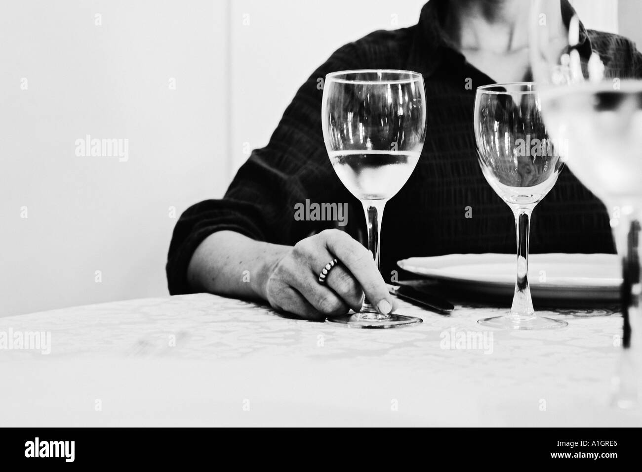 Woman At Dinner Table Holding Glass - Stock Image