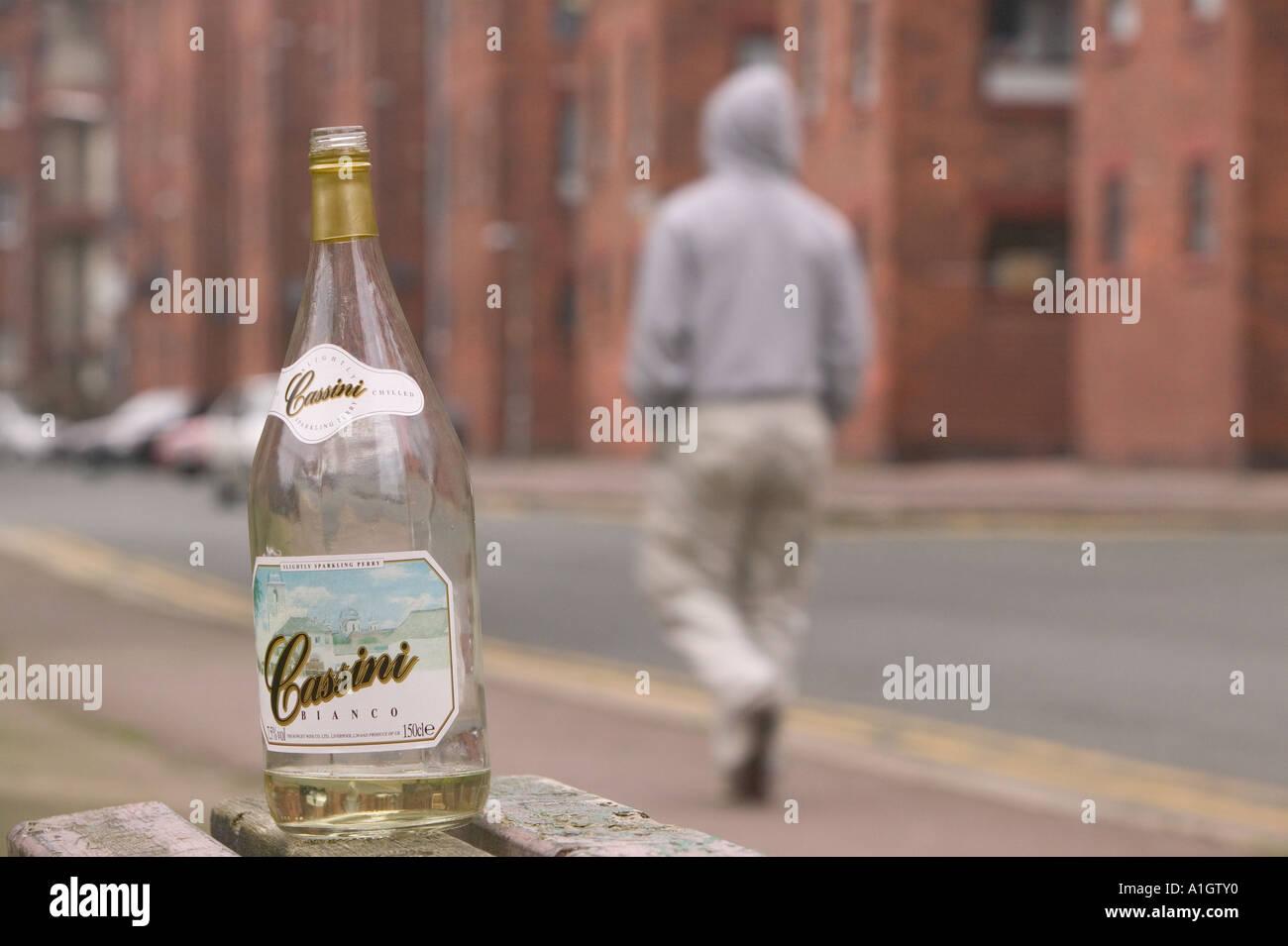 a hoody wearing youth walks past an abandoned wine bottle on Barrow island, Barrow in Furness, Cumbria, UK Stock Photo