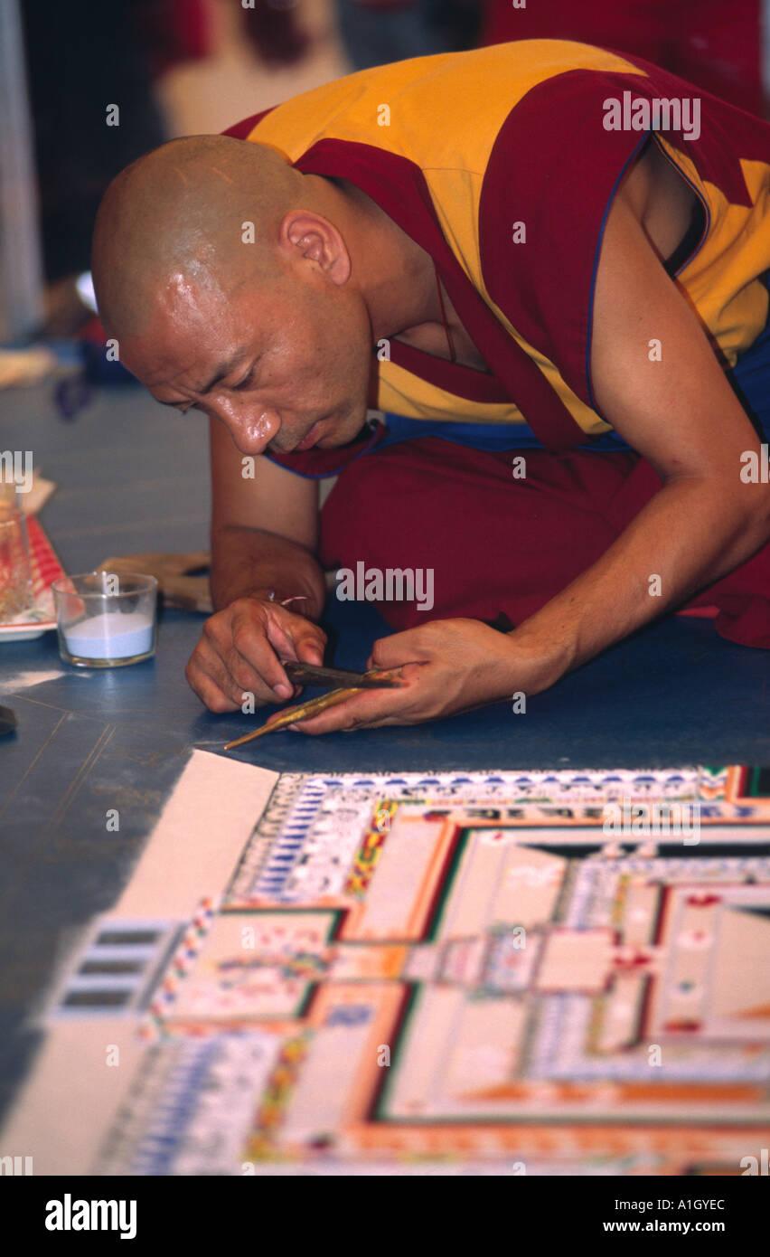 Tibetan Monk making a Mandala of colored sand  - Stock Image