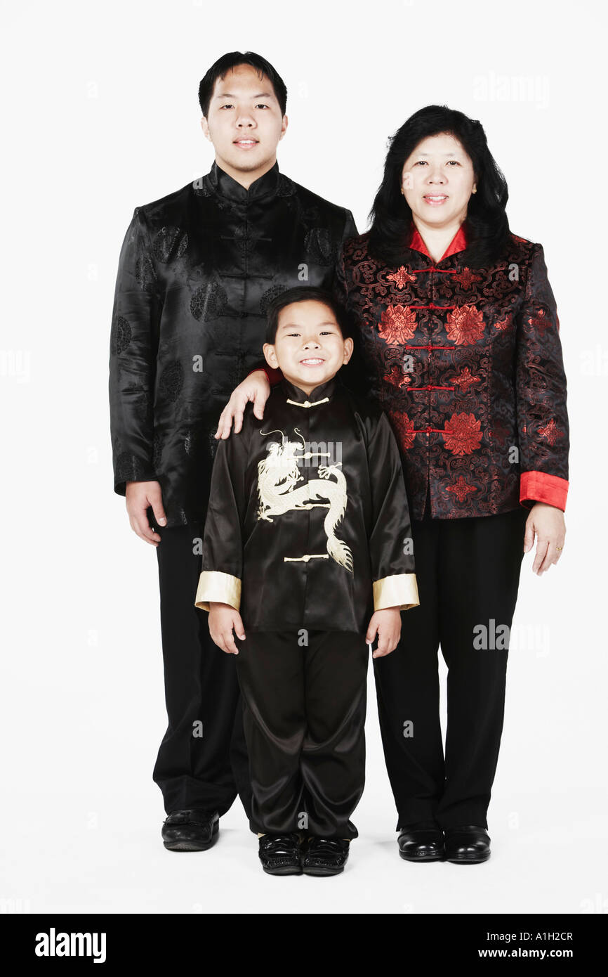 Portrait of a mother standing with her two sons smiling - Stock Image