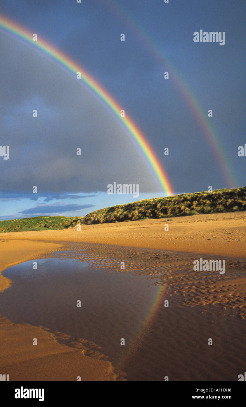 A double rainbow over the beach at Embleton Bay on the Northumberland coast - Stock Image