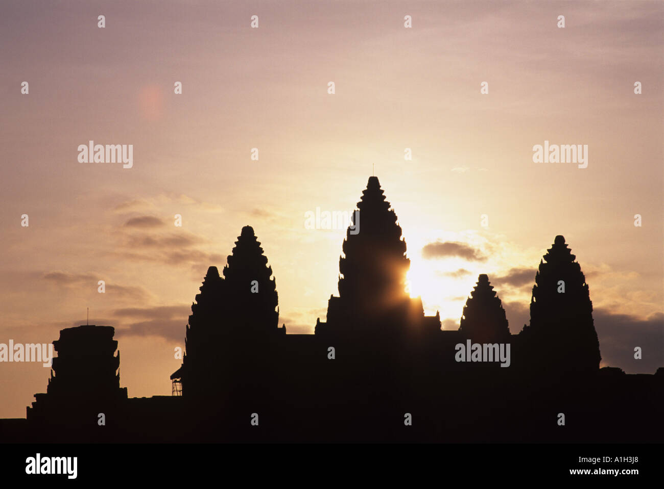 Angkor Wat in Cambodia seen here at at sunrise is a temple complex and the largest religious monument in the world Stock Photo
