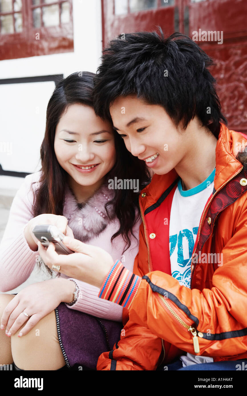Teenage boy sitting with a young woman holding a mobile phone - Stock Image