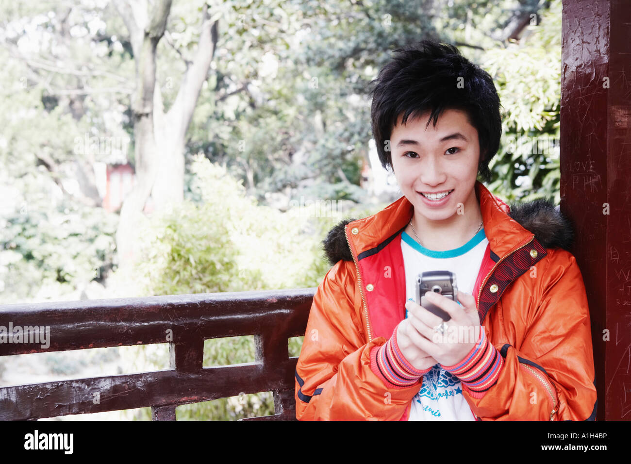 Portrait of a teenage boy holding a mobile phone smiling - Stock Image
