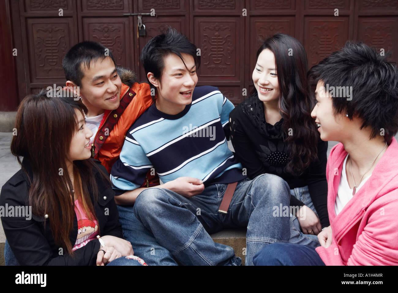 Two young men talking to two young women and a teenage boy Stock Photo