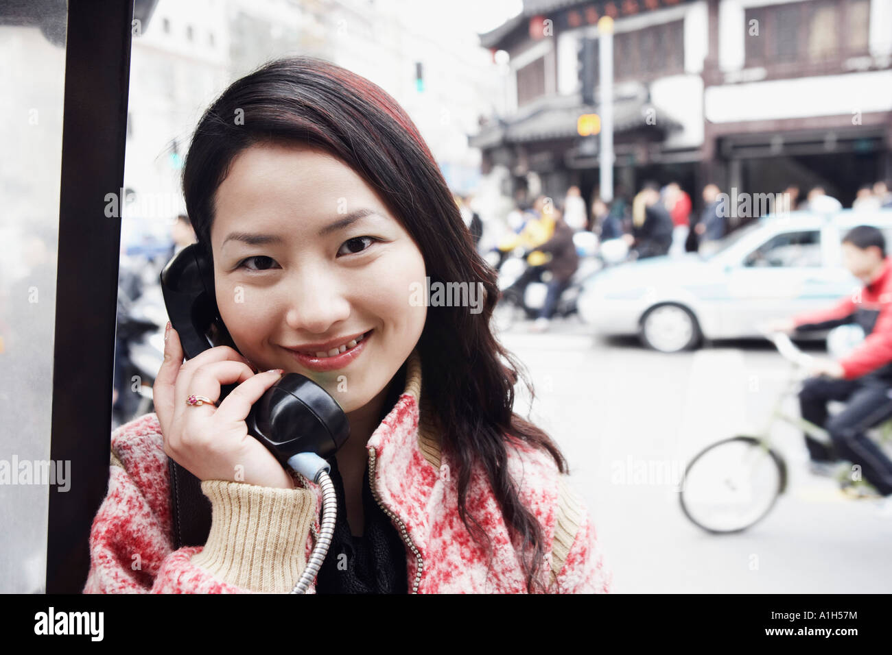 Portrait of a young woman using a telephone - Stock Image
