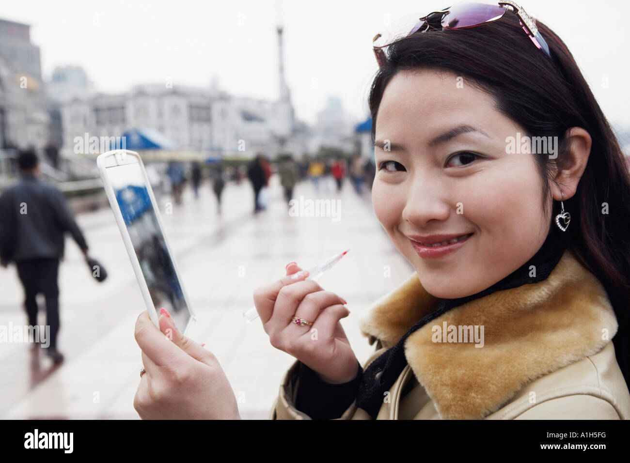Side profile of a young woman holding a mirror smiling - Stock Image