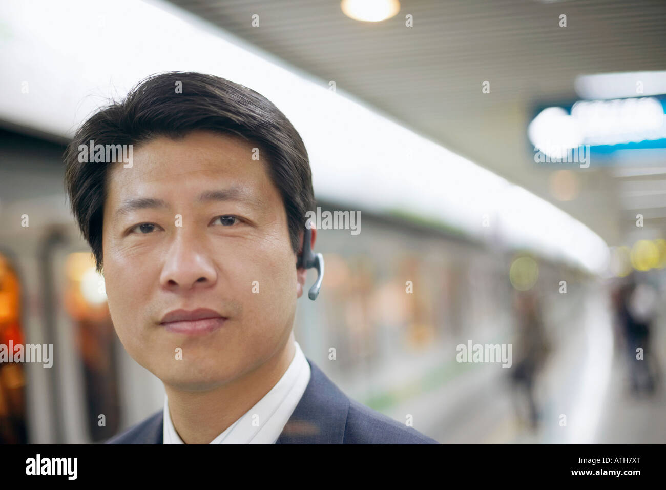 Portrait of a businessman wearing a hands free device at a subway station - Stock Image