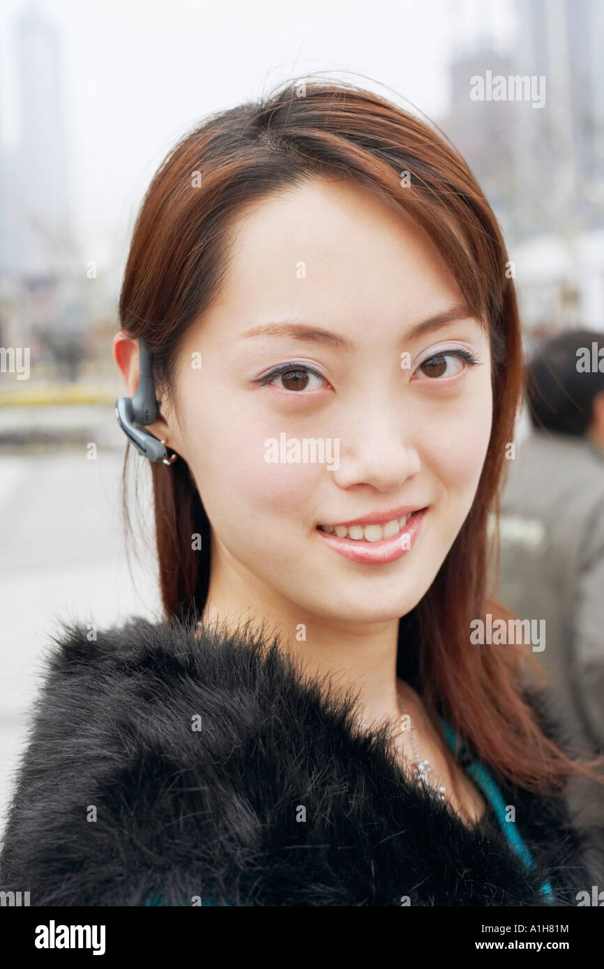 Portrait of a young woman wearing a hands free device - Stock Image