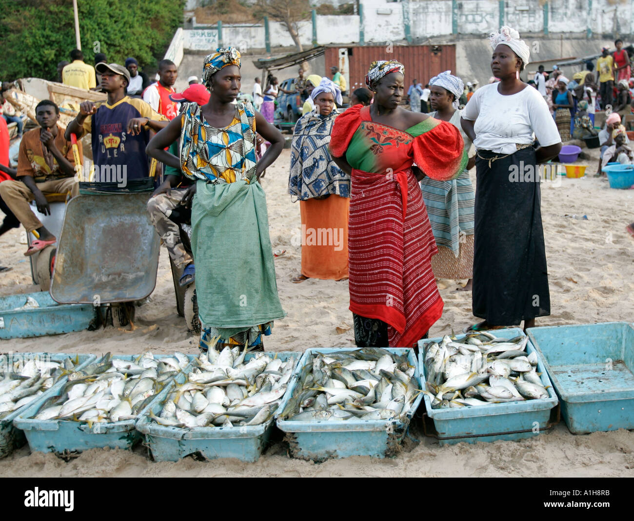 Women in colorful traditional clothes with fish for sale on beach ...
