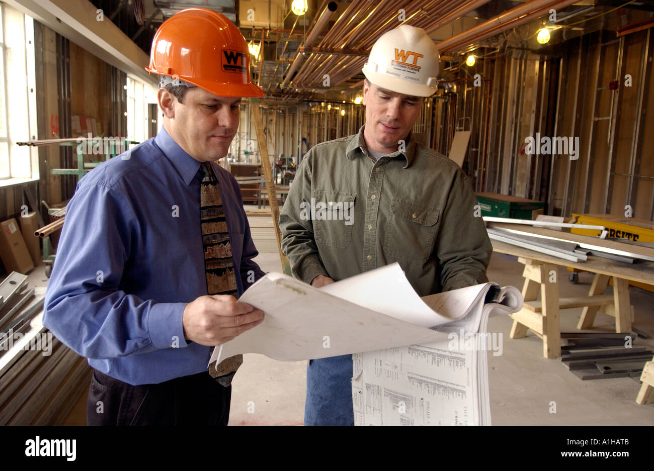 Architect and Construction foreman look over schematic drawings blueprints at construction site - Stock Image