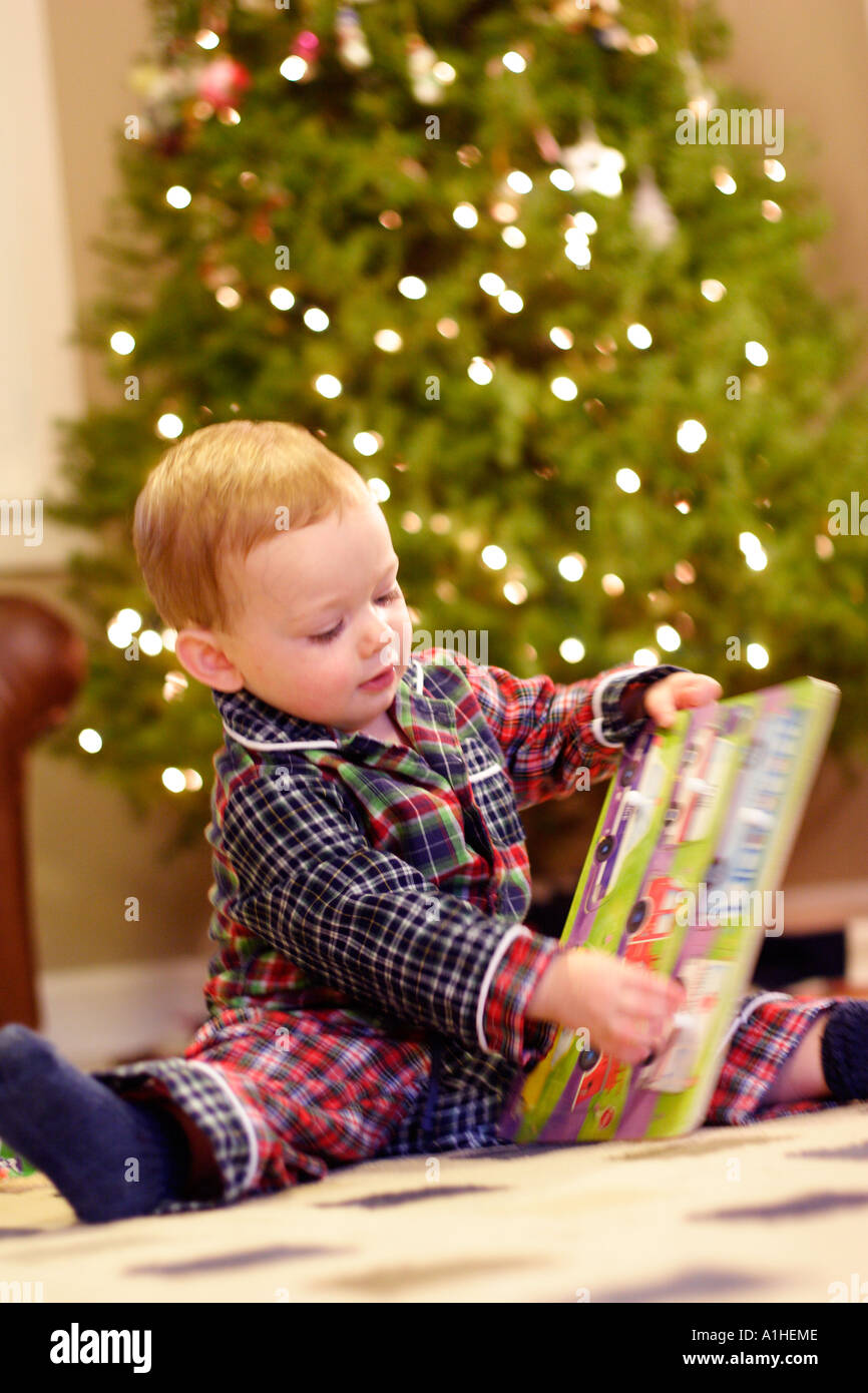 18 month old boy opening presents on Christmas morning. - Stock Image