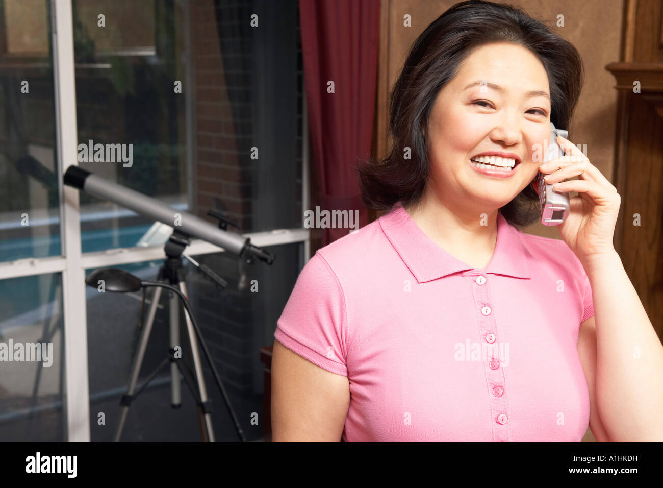 Portrait of a mature woman talking on a cordless telephone - Stock Image
