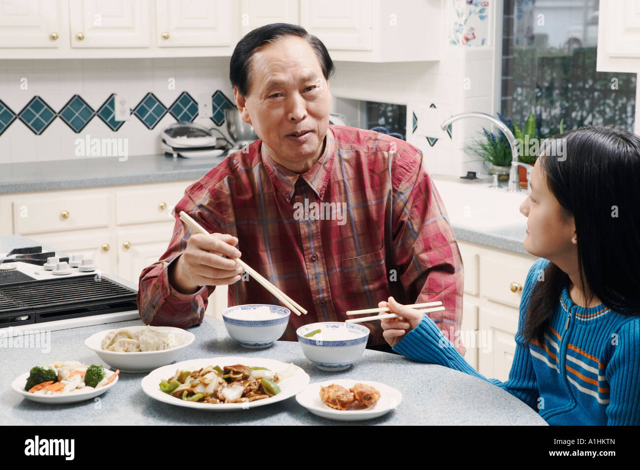 Grandfather and his granddaughter sitting at a table - Stock Image