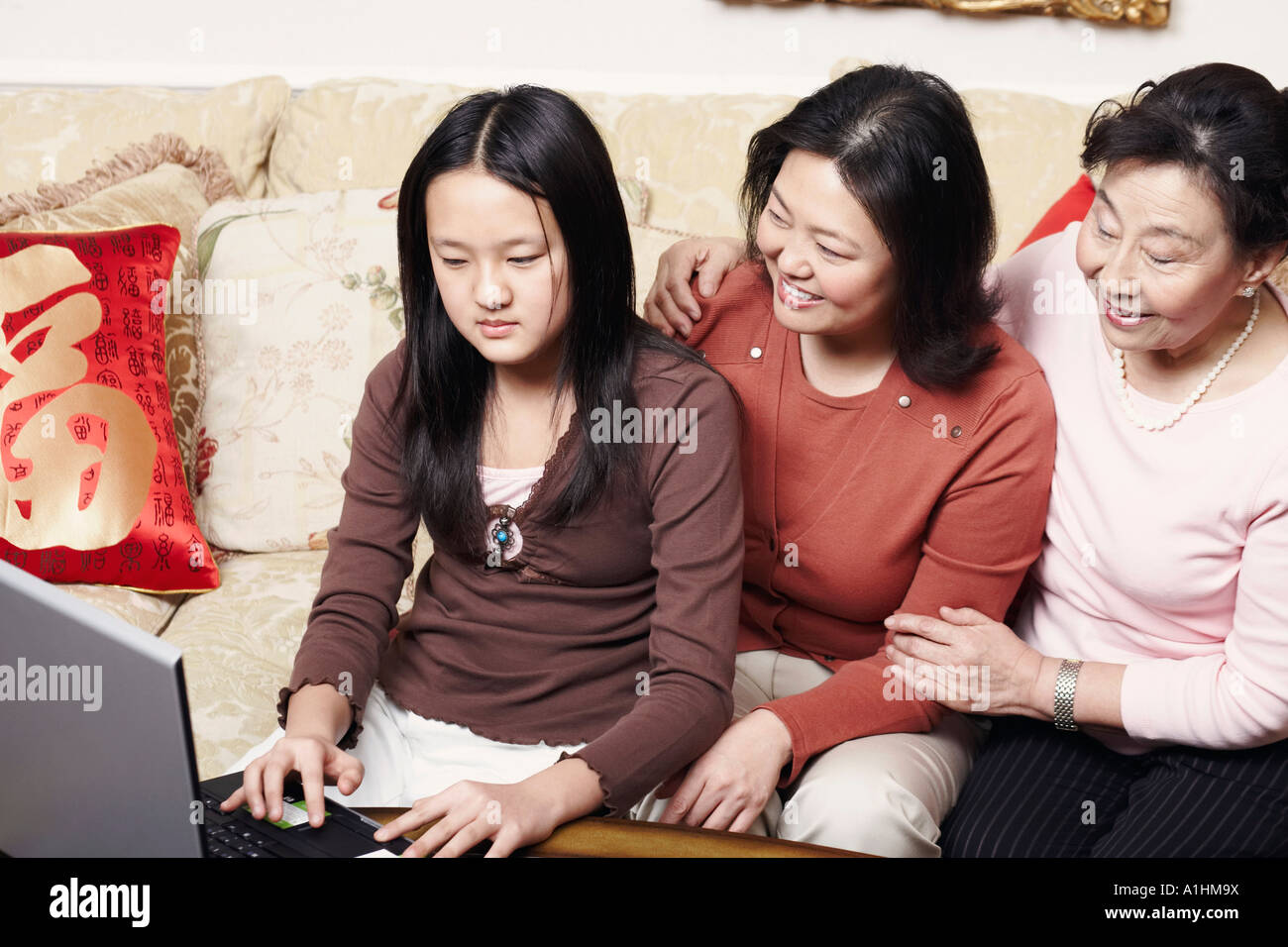 Close-up of a daughter using a laptop with her mother and her grandmother sitting beside her - Stock Image