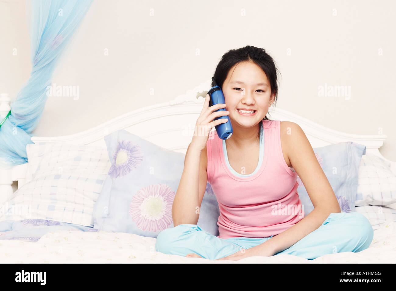 Portrait of a girl using a cordless telephone - Stock Image