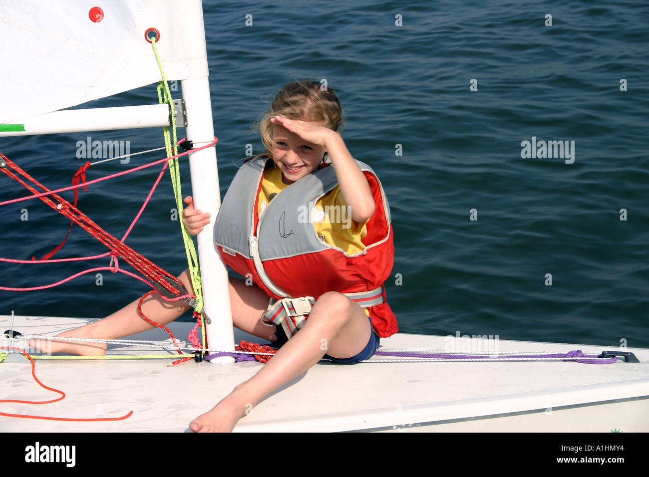 Young girl happily sitting on the foredeck of a laser sailing dinghy Stock Photo