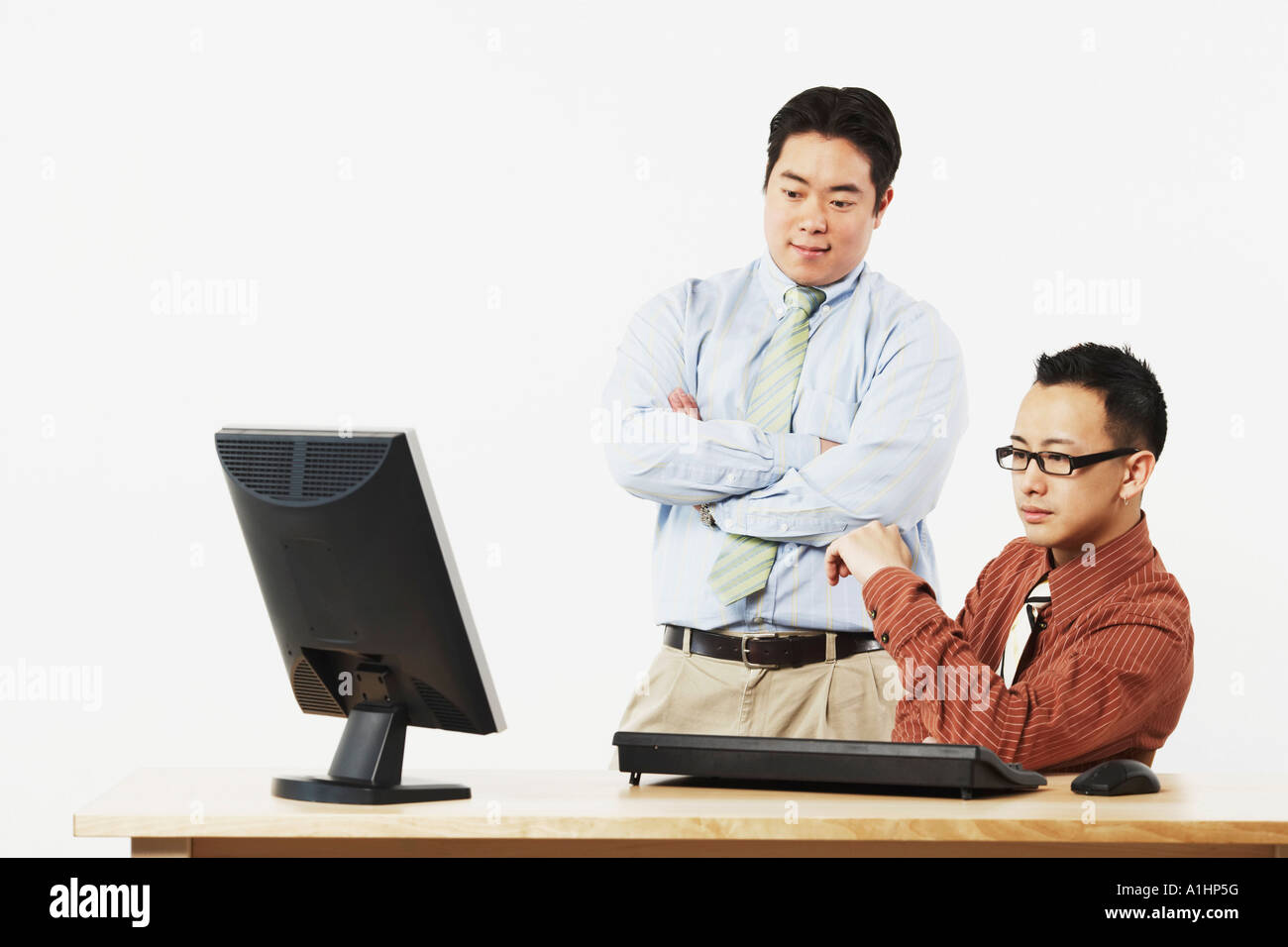 Two businessmen looking at a flat screen monitor - Stock Image