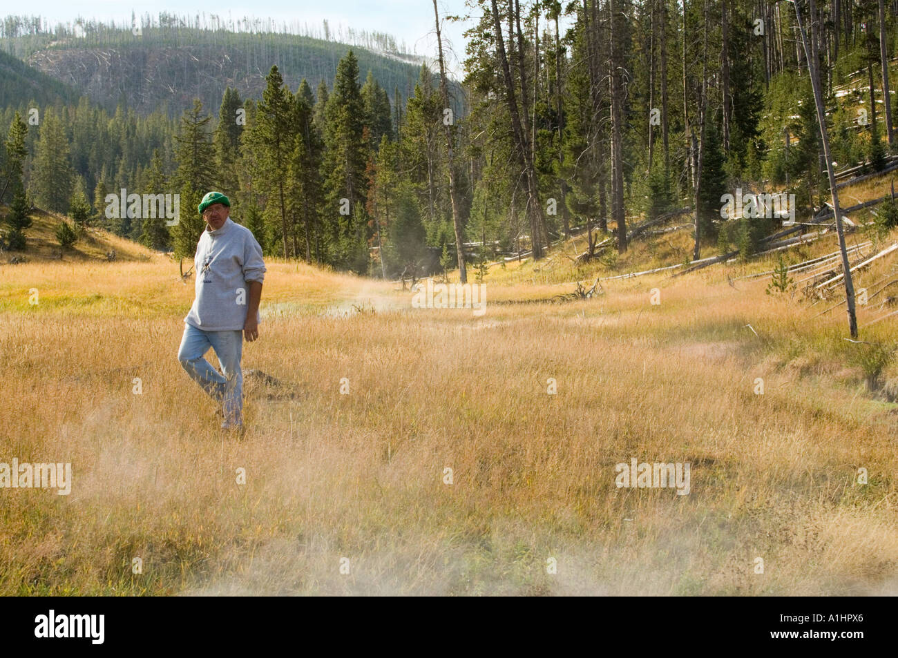 Stan Osolinski, nature photographer and teacher, walking on volcanically active meadow, Yellowstone National Park, Wyoming, USA - Stock Image