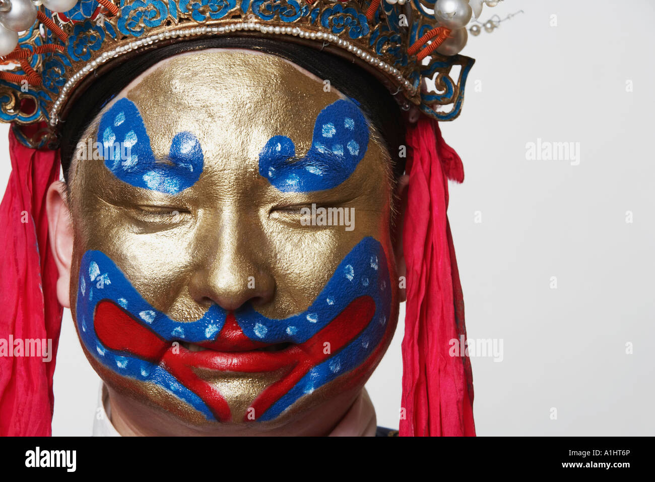 Close-up of a male Chinese opera performer with his eyes closed - Stock Image