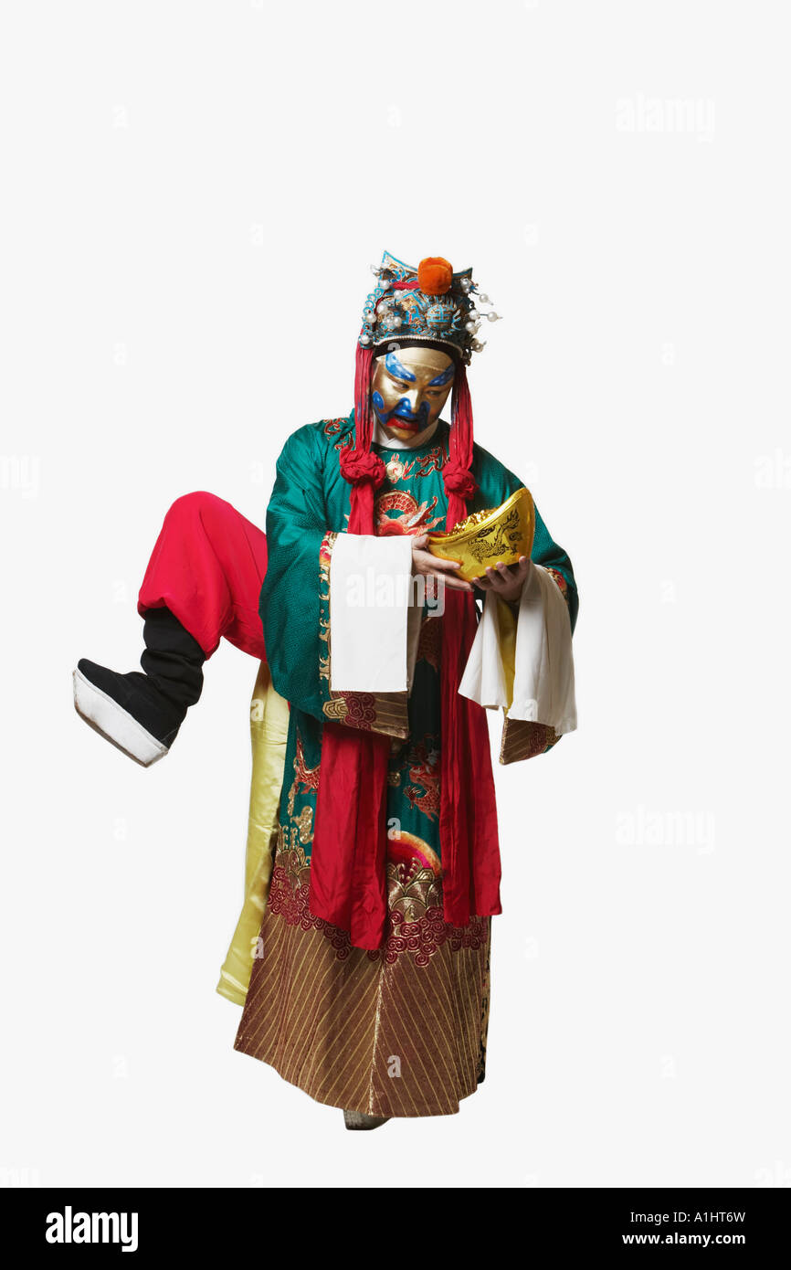 Male Chinese opera performer standing on one leg holding a bowl full of gold coins - Stock Image
