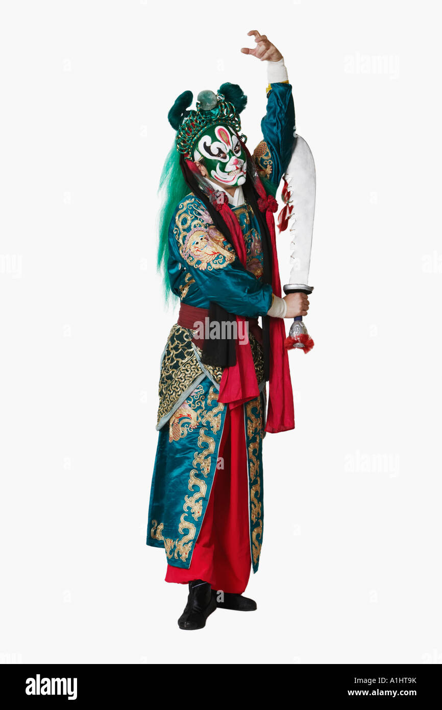 Portrait of a male Chinese opera performer standing holding a sword - Stock Image
