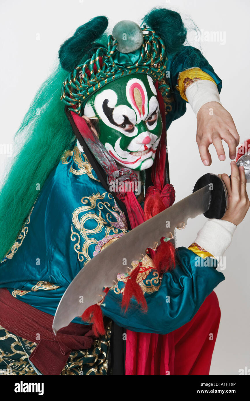 Side profile of a male Chinese opera performer holding a weapon - Stock Image