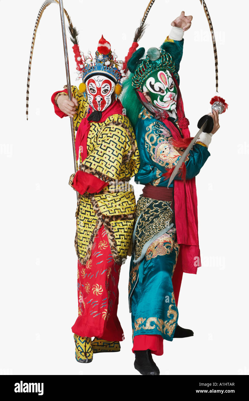 Side profile of two male Chinese opera performers gesturing with weapons - Stock Image