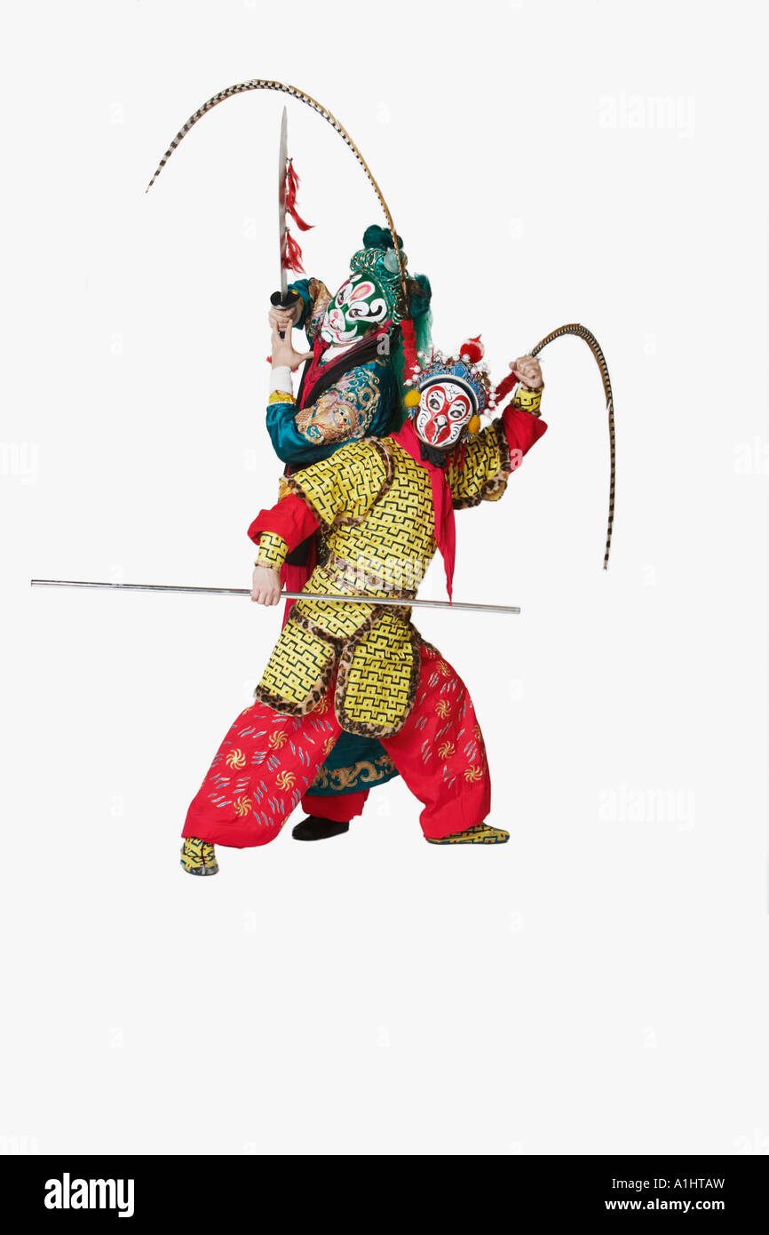 Two male Chinese opera performers gesturing with weapons - Stock Image