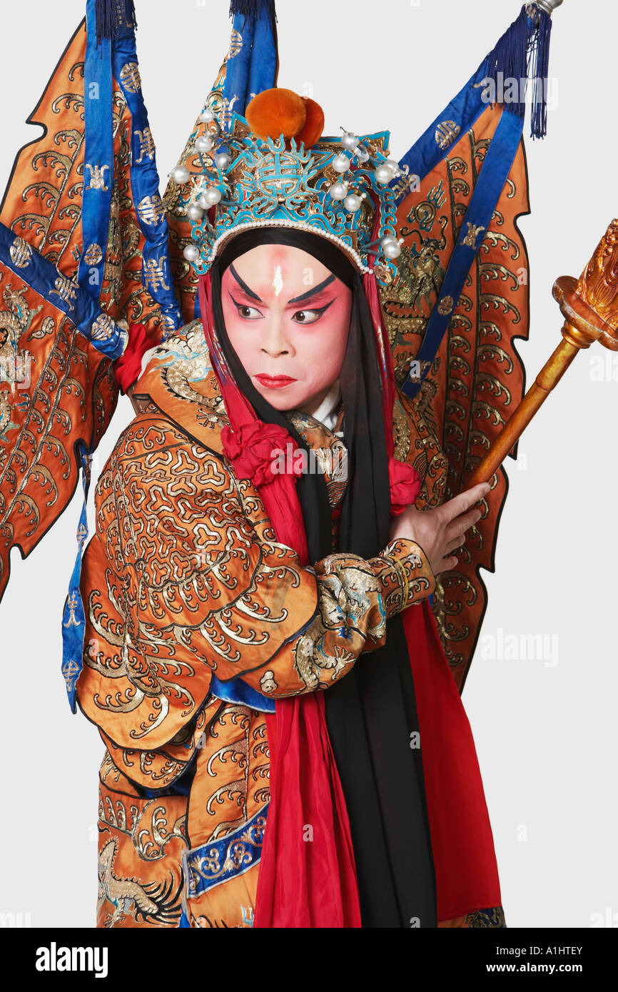 Close-up of a male Chinese opera performer holding a weapon - Stock Image