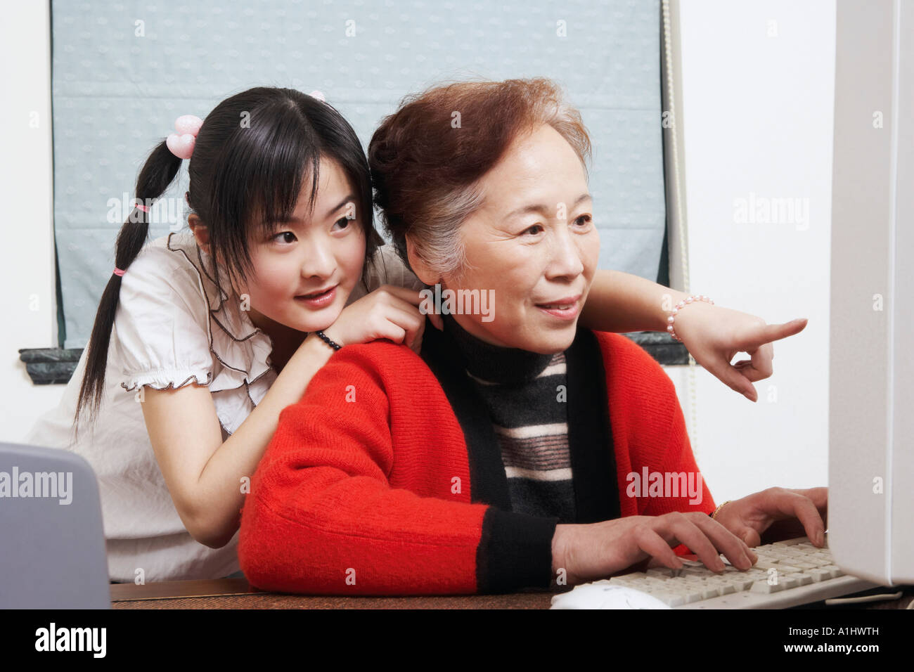Close-up of a grandmother and her granddaughter using a computer - Stock Image