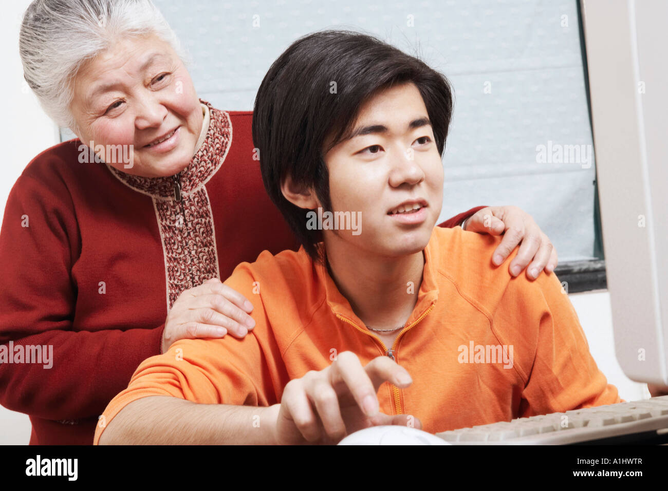 Close-up of a grandson using a computer with his grandmother standing behind him - Stock Image