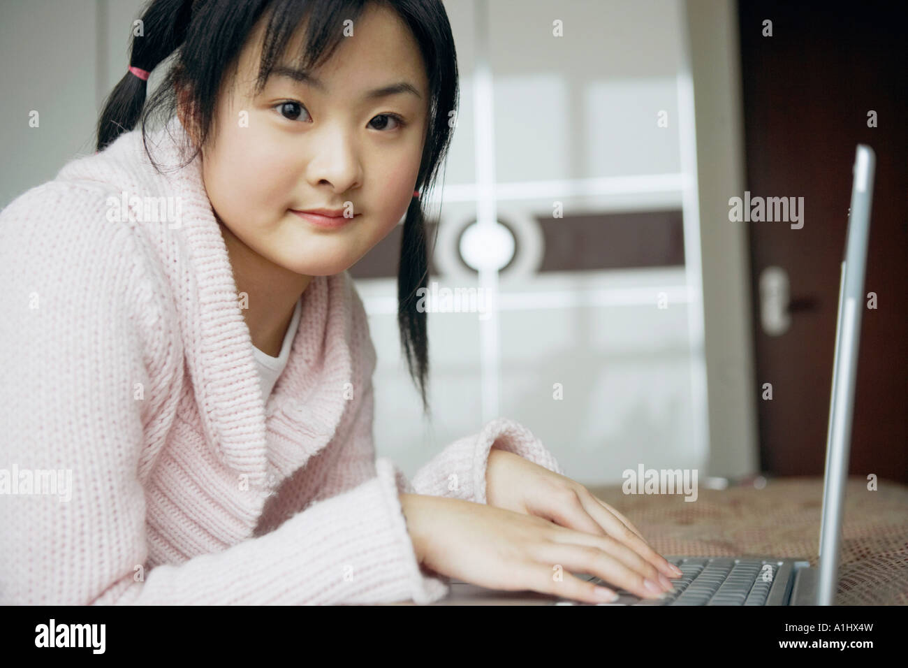 Portrait of a young woman using a laptop - Stock Image