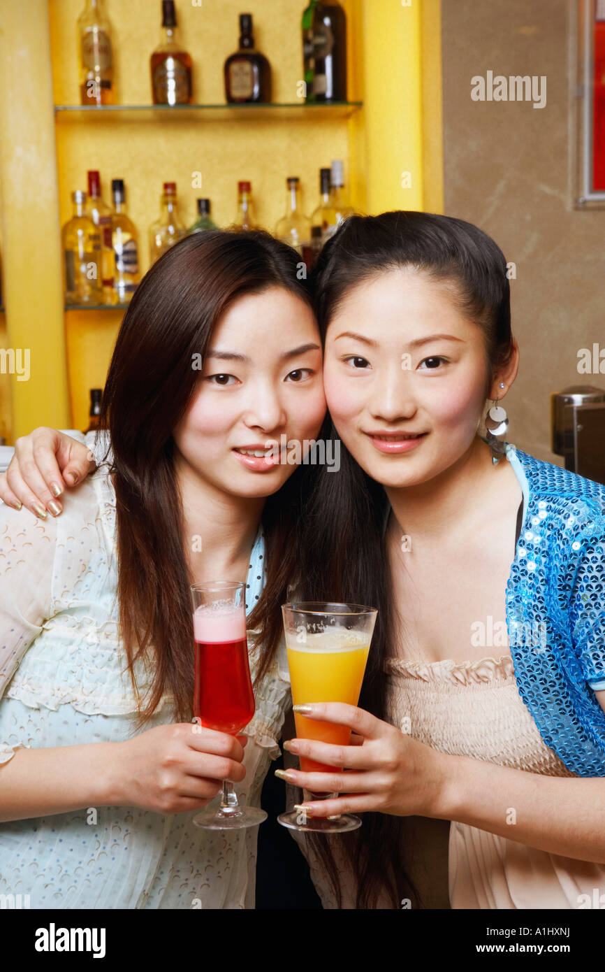 Portrait of a teenage girl and a young woman holding drinks - Stock Image