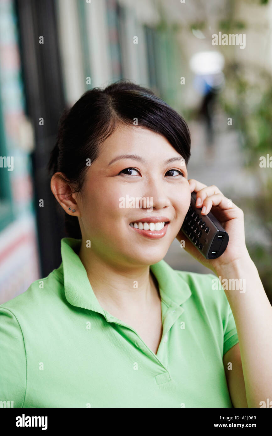 Portrait of a young woman talking on a cordless phone - Stock Image