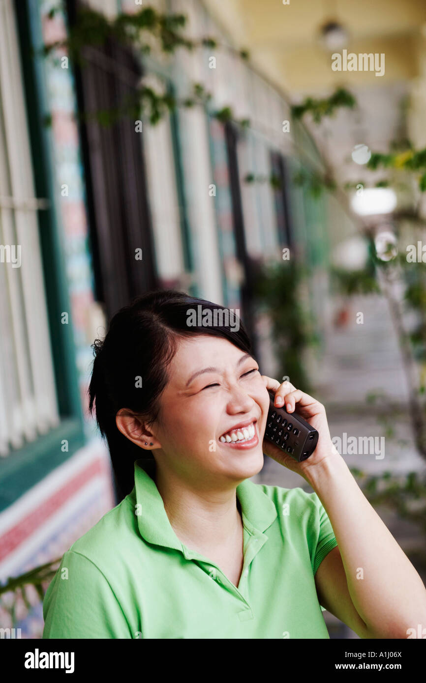 Close-up of a young woman talking on a cordless phone - Stock Image