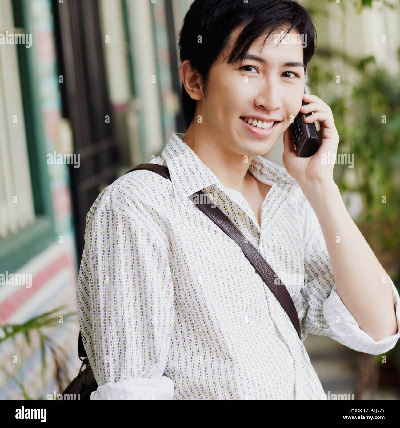 Portrait of a young man talking on a cordless phone - Stock Image