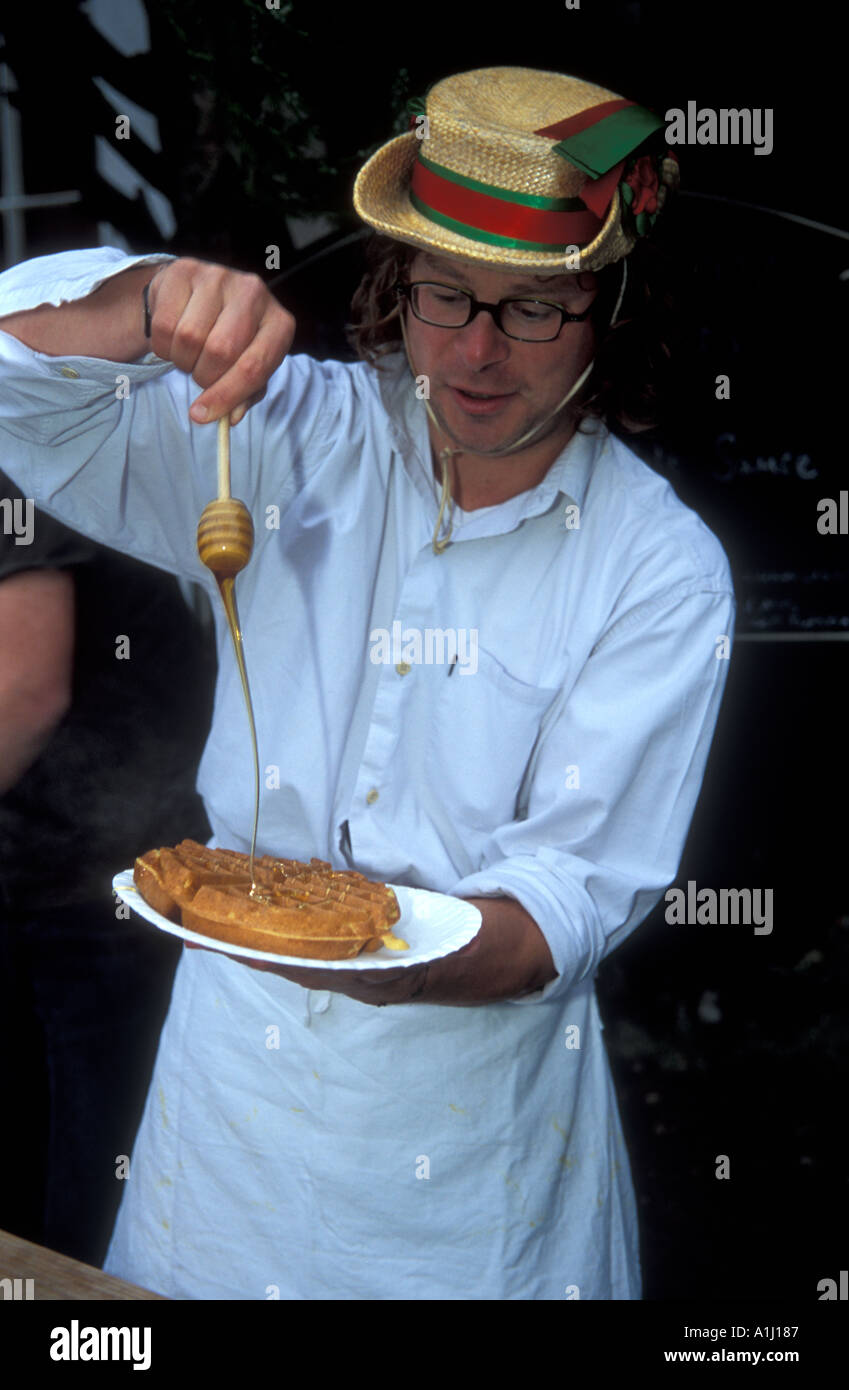 Man cooking waffles at a street festival United Kingdom - Stock Image