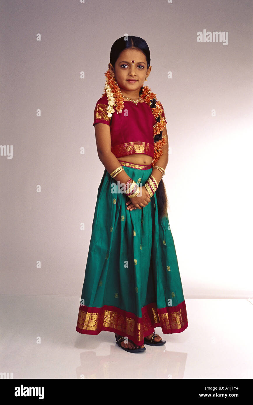 0f90a391fa Young South Indian girl standing white background wearing traditional  costume dress ghagra choli skirt top flowers gajra in hair