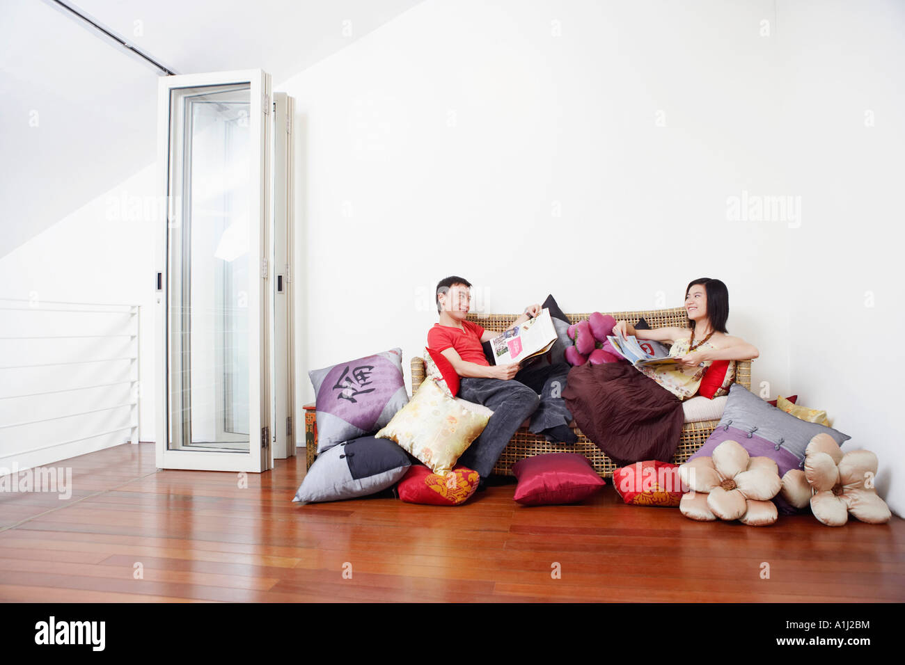 Side profile of a mid adult man with a young woman reclining on a couch and looking at each other Stock Photo
